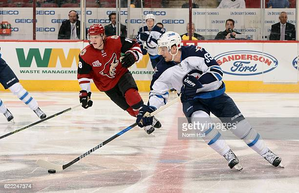 Mark Scheifele of the Winnipeg Jets skates with the puck ahead of Christian Dvorak of the Arizona Coyotes during the second period at Gila River...