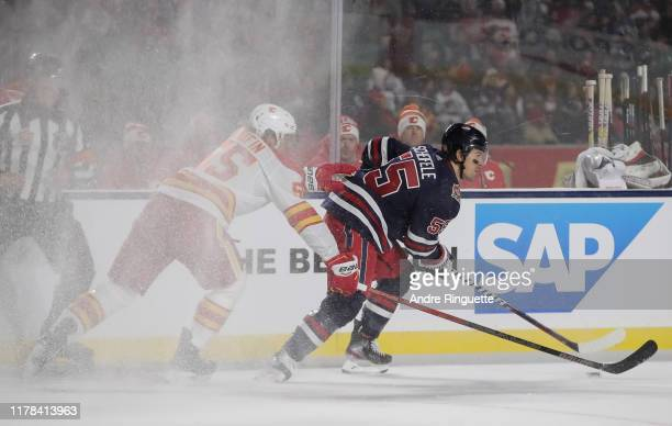 Mark Scheifele of the Winnipeg Jets stickhandles the puck away from Noah Hanifin of the Calgary Flames during the 2019 Tim Hortons NHL Heritage...