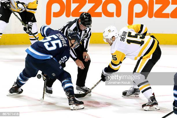 Mark Scheifele of the Winnipeg Jets takes a second period faceoff against Riley Sheahan of the Pittsburgh Penguins at the Bell MTS Place on October...