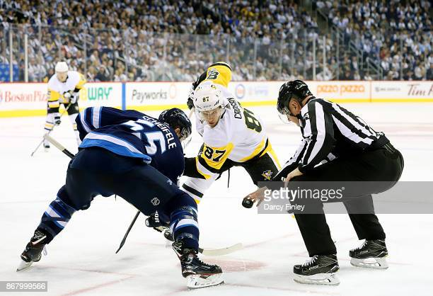 Mark Scheifele of the Winnipeg Jets takes a third period faceoff against Sidney Crosby of the Pittsburgh Penguins at the Bell MTS Place on October 29...