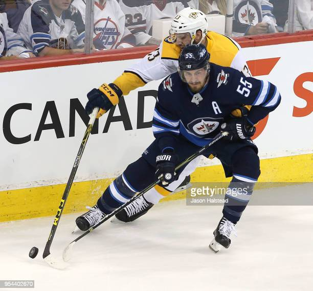 Mark Scheifele of the Winnipeg Jets works the puck past Nick Bonino of the Nashville Predators in Game Four of the Western Conference Second Round...