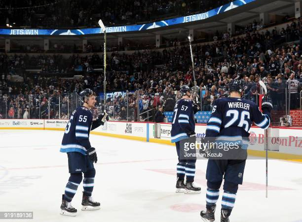 Mark Scheifele Tyler Myers and Blake Wheeler of the Winnipeg Jets salute the fans following a 61 victory over the Colorado Avalanche at the Bell MTS...