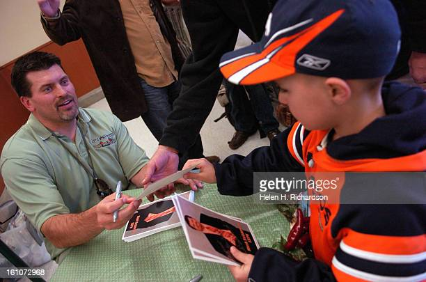 Mark Schlereth left signs and autographs a picture of himself for 6 year old Kaleb Hacker <cq> His father Rodney Hacker is at right next to Kaleb...