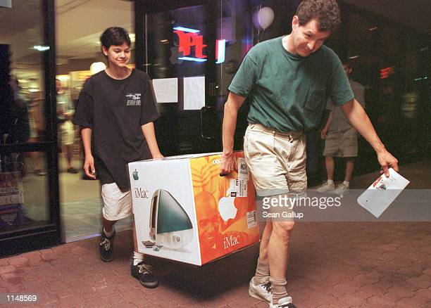 Mark Seigel and his son David carry away their just purchased Apple MacIntosh iMac computer at a dealership in Bethesda Maryland just minutes after...
