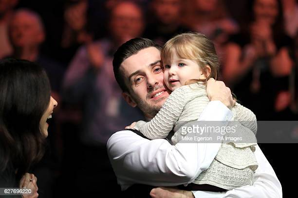 Mark Selby celebrates his victory over Ronnie O'Sullivan with his daughter Sofia Maria and wife Vikki Layton during day twelve of the Betway UK...