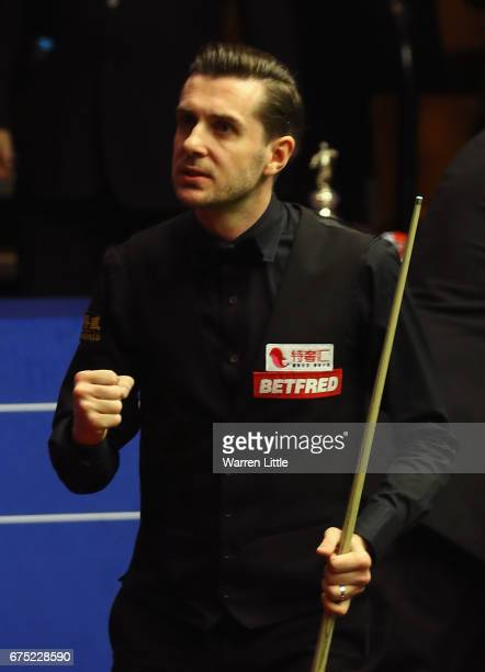 Mark Selby of England celebrates winning a frame during the final against John Higgins of Scotland on day sixteen at Crucible Theatre on April 30...