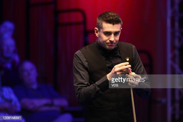Mark Selby of England chalks the cue during a quarterfinal match against Stephen Maguire of Scotland on day four of 2020 Coral Players Championship...