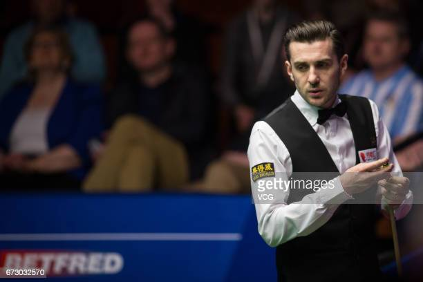 Mark Selby of England chalks the cue during his quarter final match against Marco Fu of Chinese Hong Kong on day eleven of Betfred World Championship...