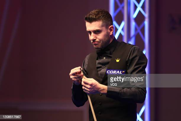 Mark Selby of England chalks the cue during the 1st round match against Mark Williams of Wales on day one of the 2020 Coral Players Championship at...
