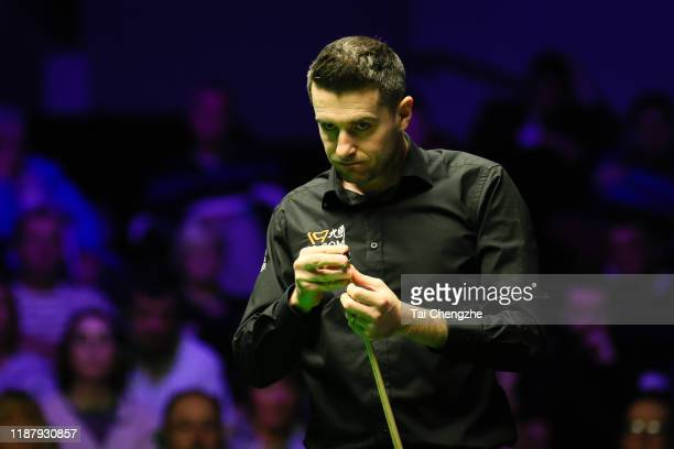 Mark Selby of England chalks the cue during the quarterfinal match against John Higgins of Scotland on day five of 2019 Northern Ireland Open at...