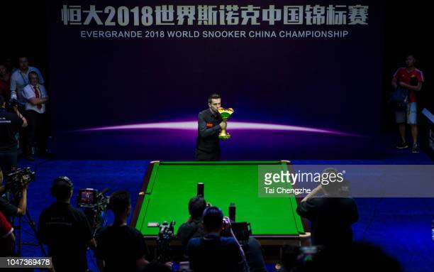 Mark Selby of England kisses his trophy after winning the final match against John Higgins of Scotland during day seven of the Evergrande 2018 World...