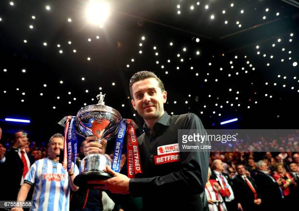 Mark Selby of England poses with the trophy after beating John Higgins of Scotland in the final of the World Snooker Championship on day seventeen at...