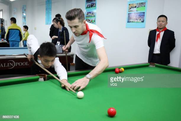 Mark Selby of England teaches students snooker at a primary school during the 2017 CBSA Haining Internation Snooker Open on October 25 2017 in...