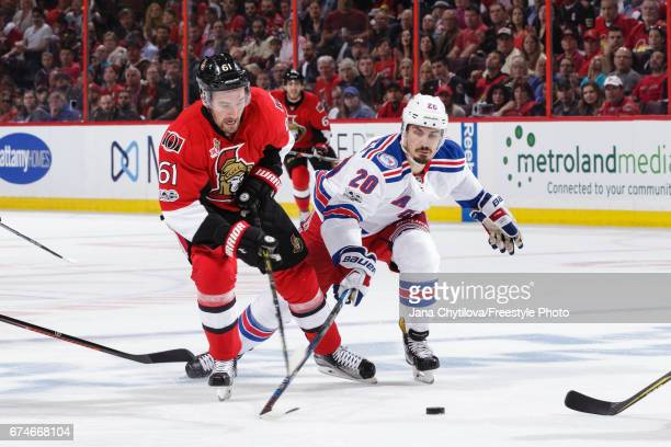 Mark Stone of the Ottawa Senators battles for the loose puck against Chris Kreider of the New York Rangers in Game One of the Eastern Conference...