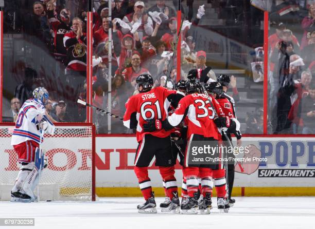 Mark Stone of the Ottawa Senators celebrates his first period goal withbteammates Fredrik Claesson and Chris Wideman as Henrik Lundqvist of the New...