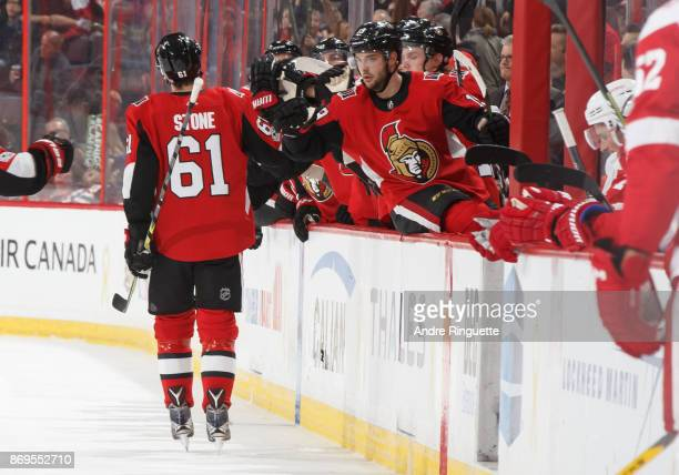 Mark Stone of the Ottawa Senators celebrates his first period goal against the Detroit Red Wings with teammate Derick Brassard at the players' bench...