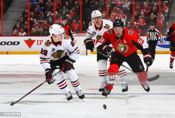 Mark Stone of the Ottawa Senators chases down a loose puck with Henri Jokiharju of the Chicago Blackhawks at Canadian Tire Centre on October 4 2018...