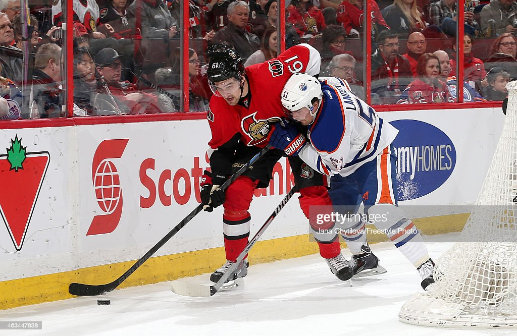 Mark Stone #61 of the Ottawa Senators gets to the puck ahead of Anton Lander #51 of the Edmonton Oilers at Canadian Tire Centre on February 14, 2015 in Ottawa, Ontario, Canada.