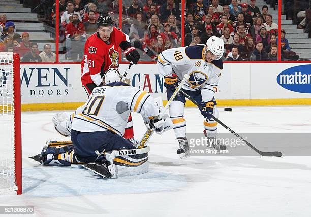 Mark Stone of the Ottawa Senators looks for a rebound as Robin Lehner and William Carrier of the Buffalo Sabres defend their net at Canadian Tire...