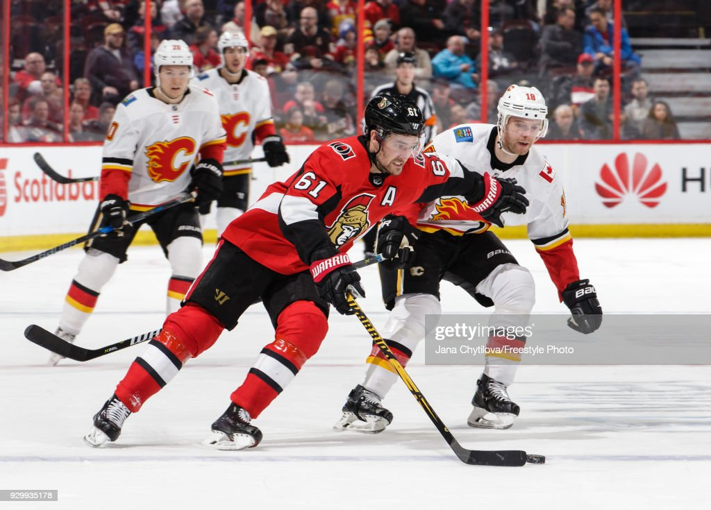Mark Stone #61 of the Ottawa Senators protects the puck from Matt Stajan #18 of the Calgary Flames in the third period at Canadian Tire Centre on March 9, 2018 in Ottawa, Ontario, Canada.