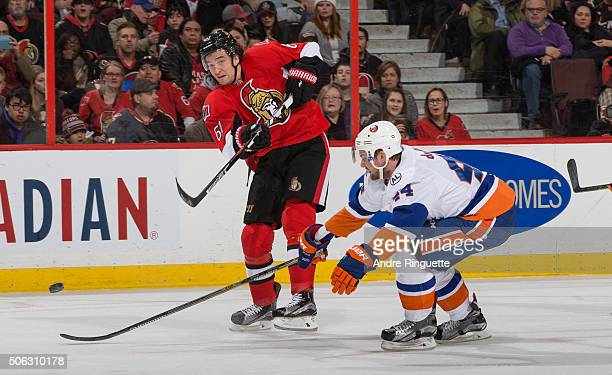 Mark Stone of the Ottawa Senators shoots the puck against Calvin de Haan of the New York Islanders at Canadian Tire Centre on January 22 2016 in...