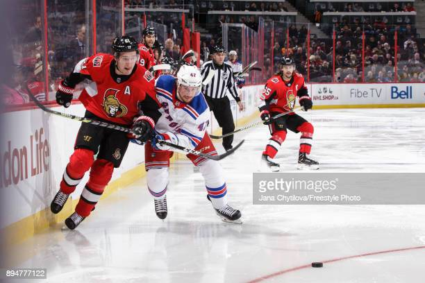 Mark Stone of the Ottawa Senators skates against Brendan Smith of the New York Rangers for the puck at Canadian Tire Centre on December 13 2017 in...