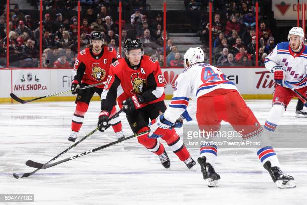 Mark Stone of the Ottawa Senators skates with the puck against Brendan Smith of the New York Rangers at Canadian Tire Centre on December 13 2017 in...