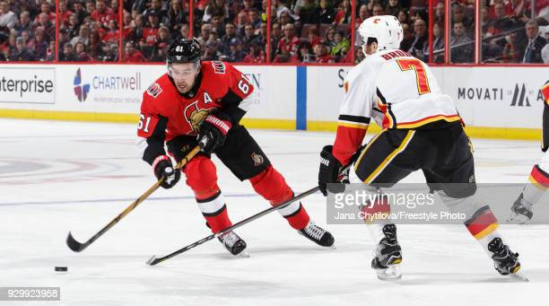 Mark Stone of the Ottawa Senators skates with the puck against TJ Brodie of the Calgary Flames in the second period at Canadian Tire Centre on March...