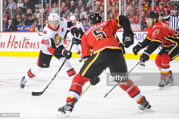 Mark Stone of the Ottawa Senators skates with the puck as Mark Giordano and Dougie Hamilton of the Calgary Flames defend during an NHL game at...