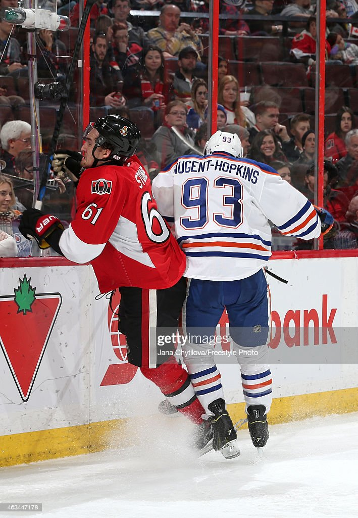 Mark Stone #61 of the Ottawa Senators xgets checked into the boards by Ryan Nugent-Hopkins #93 of the Edmonton Oilers in the third period at Canadian Tire Centre on February 14, 2015 in Ottawa, Ontario, Canada.