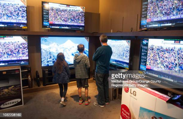Mark Stoner of San Juan Capistrano and his children Jeremy 11 and Natalie take a moment to gaze at 4K televisions at Paul's TV and Appliances in...