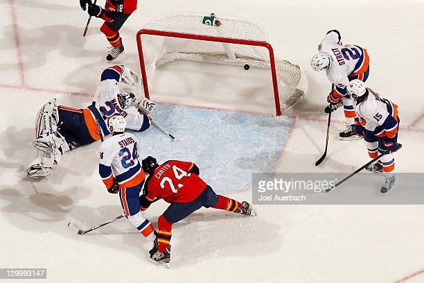 Mark Streit and PA Parenteau of the New York Islanders look into the net as the puck shot by Matt Bradley of the Florida Panthers scores a goal in...