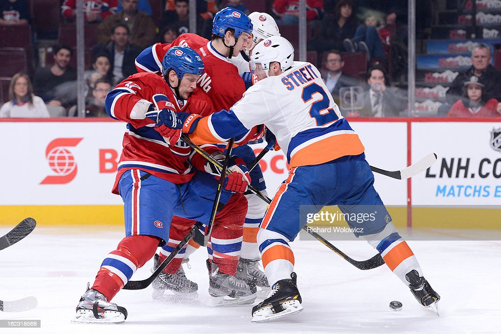Mark Streit #2 of the New York Islanders defends against Travis Moen #32 of the Montreal Canadiens during the NHL game at the Bell Centre on February 21, 2013 in Montreal, Quebec, Canada. The Islanders defeated the Canadiens 4-3 in overtime.