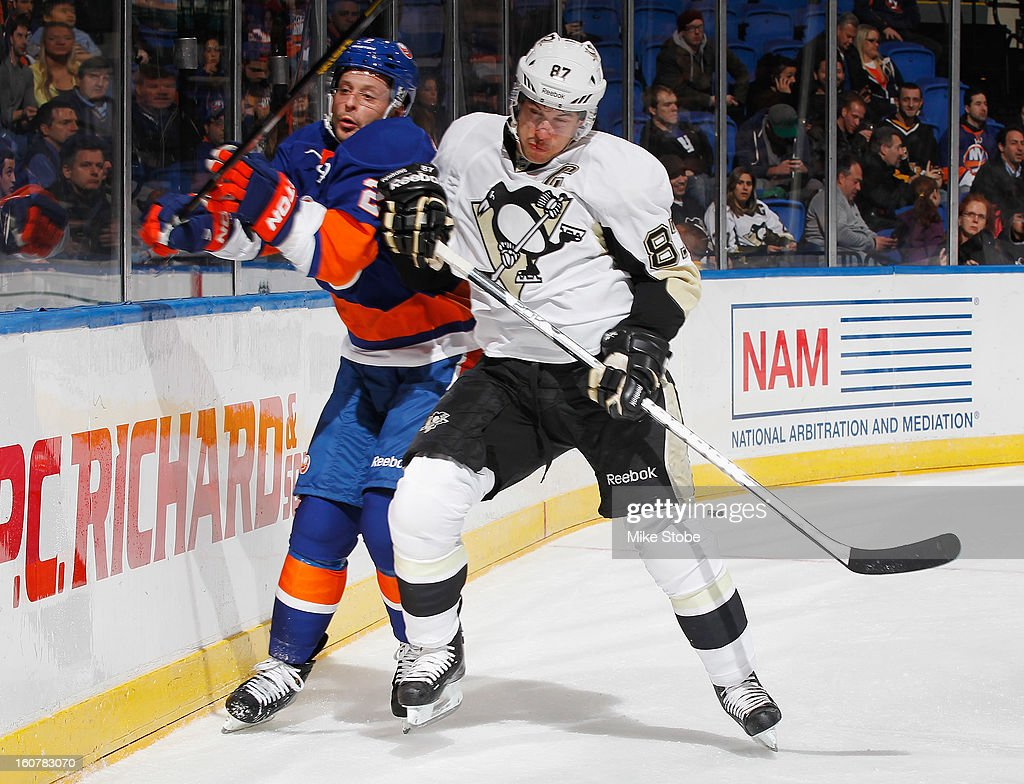 Mark Streit #2 of the New York Islanders is checked by Sidney Crosby #87 of the Pittsburgh Penguins at Nassau Veterans Memorial Coliseum on February 5, 2013 in Uniondale, New York.