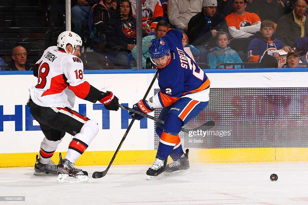 Mark Streit #2 of the New York Islanders skates against Jim O'Brien #18 of the Ottawa Senators during their game at Nassau Veterans Memorial Coliseum on March 3, 2013 in Uniondale, New York.