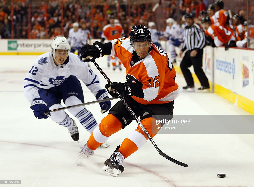 Mark Streit #32 of the Philadelphia Flyers moves the puck away from Mason Raymond #12 of the Toronto Maple Leafs during the third period at Wells Fargo Center on March 28, 2014 in Philadelphia, Pennsylvania. The Flyers defeated the Maple Leafs 4-2.