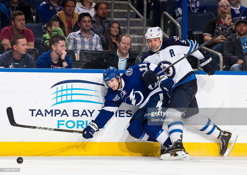 Mark Stuart #5 of the Winnipeg Jets checks Tom Pyatt #11 of the Tampa Bay Lightning during the third period of the game at the Tampa Bay Times Forum on March 7, 2013 in Tampa, Florida.