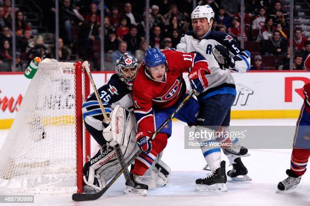 Mark Stuart of the Winnipeg Jets clears Brendan Gallagher of the Montreal Canadiens from in front of goalie Al Montoya during the NHL game at the...