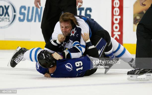 Mark Stuart of the Winnipeg Jets fights B.J. Crombeen of the Tampa Bay Lightning during the first period at Tampa Bay Times Forum on December 7, 2013...