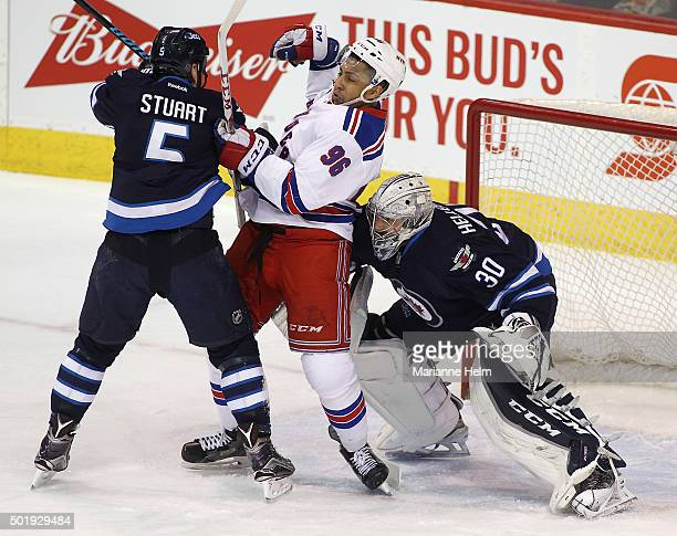 Mark Stuart of the Winnipeg Jets puts pressure on Emerson Etem of the New York Rangers as goaltender Connor Hellebuyck tries to look around them in...