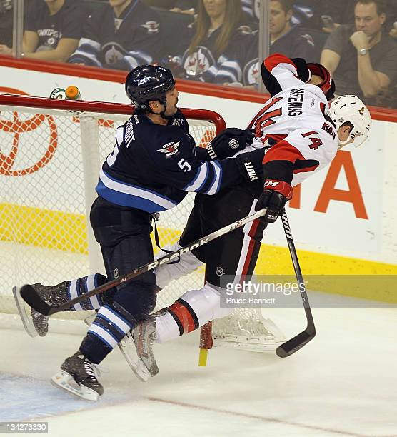 Mark Stuart of the Winnipeg Jets runs Colin Greening of the Ottawa Senators out of the crease in the third period at the MTS Centre on November 29...