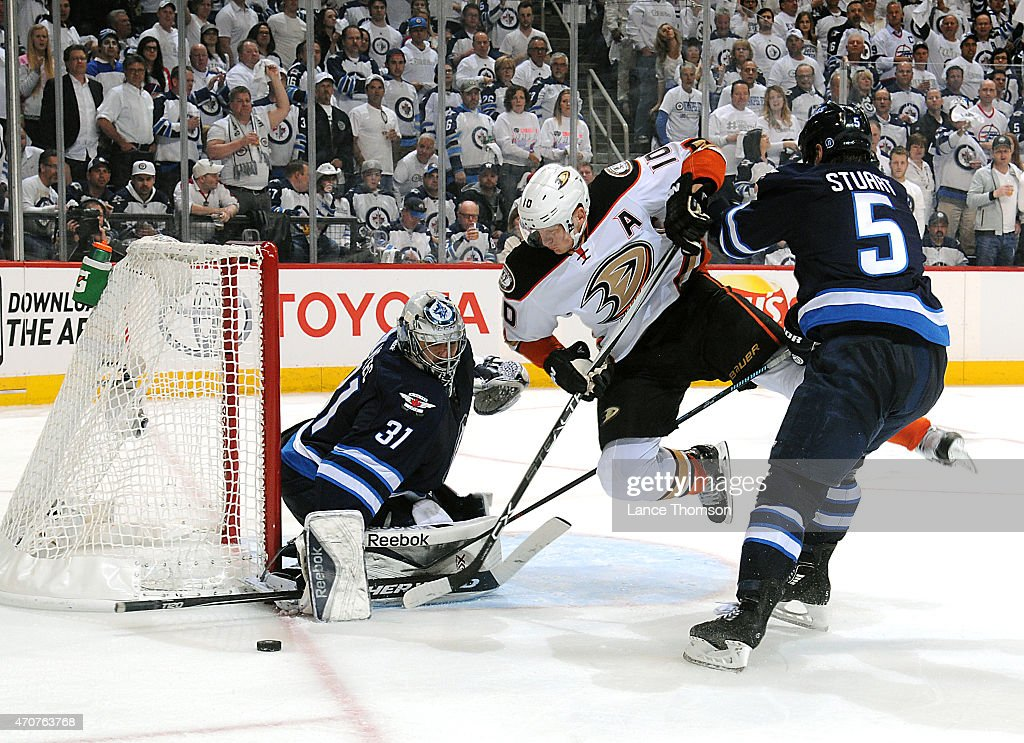 Mark Stuart #5 of the Winnipeg Jets sends Corey Perry #10 of the Anaheim Ducks flying as he chases the puck during third period action in Game Four of the Western Conference Quarterfinals during the 2015 NHL Stanley Cup Playoffs on April 22, 2015 at the MTS Centre in Winnipeg, Manitoba, Canada.