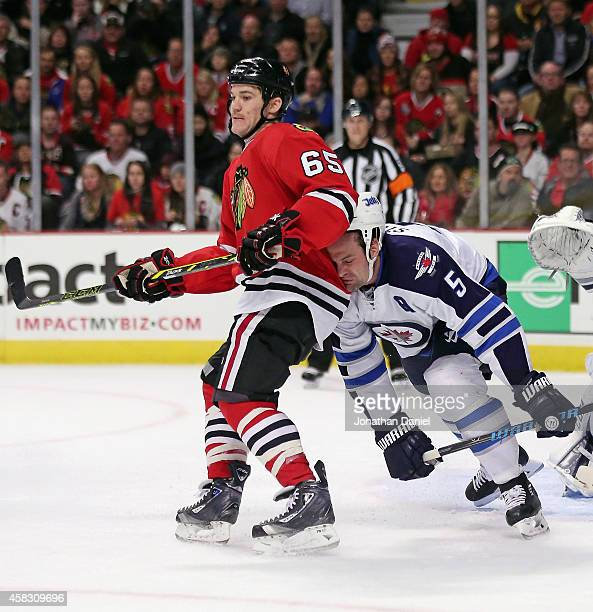 Mark Stuart of the Winnipeg Jets slips and collides with Andrew Shaw of the Chicago Blackhawks at the United Center on November 2 2014 in Chicago...