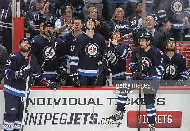 Mark Stuart Tyler Myers and Toby Enstrom of the Winnipeg Jets watch the scoreboard as a replay of a second period shorthanded goal by teammate Dustin...