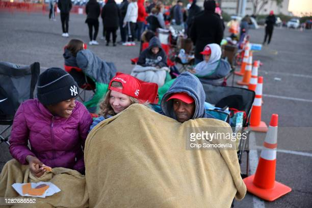 Mark Swindell and his daughters Ivy and Ella try to keep warm at dawn while waiting in line to attend a campaign rally with U.S. President Donald...