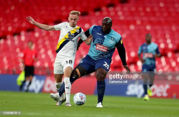 Mark Sykes of Oxford United is challenged by Adebayo Akinfenwa of Wycombe Wanderers during the Sky Bet League One Play Off Final between Oxford...