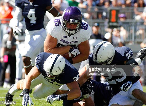 Mark Szott of the Northwestern Wildcats is tackled after catching a pass in the first half against Ryan Keiser and Charles Idemudia of the Penn State...