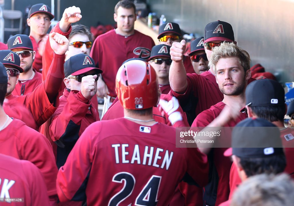 Mark Teahen #24 of the Arizona Diamondbacks is congratulated by Matt Davidson #70 (R) after Teahen scored a fourth inning run against the Kansas City Royals during the spring training game at Surprise Stadium on February 25, 2013 in Surprise, Arizona.