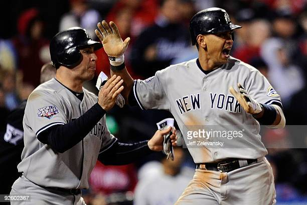 Mark Teixeira and Alex Rodriguez of the New York Yankees celebrate after they scored on a 2-run single by Jorge Posada in the top of the ninth inning...