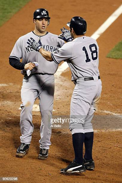Mark Teixeira and Johnny Damon of the New York Yankees celebrate after they scored on a 2run double by Alex Rodriguez in the top of the eighth inning...